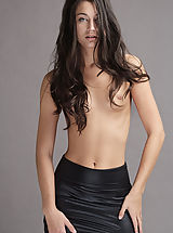 18 year old Georgia sheds her sleek black leather miniskirt and poses nude gazing into the camera with emerald green eyes.